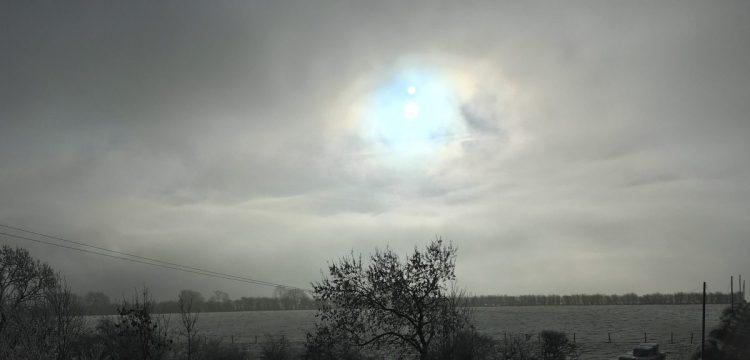Landscape photo of a misty sky over a frosty grass field.