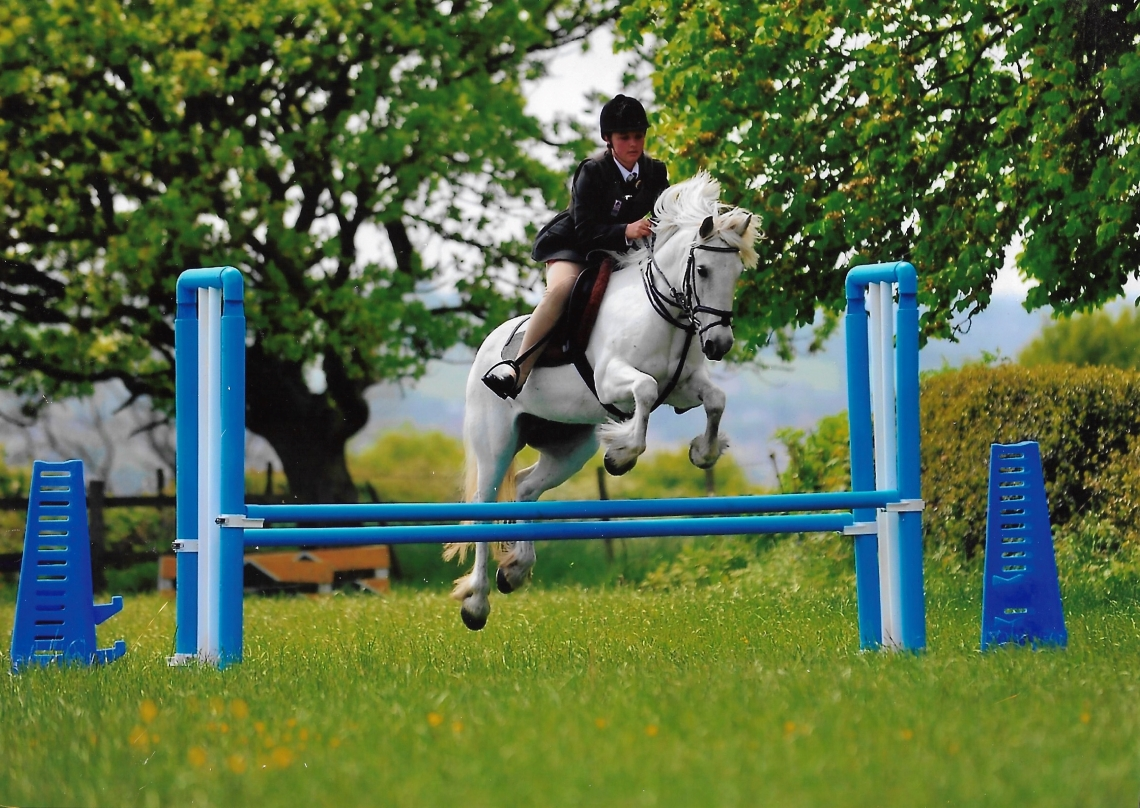 Showjumping. A girl jumping a grey fell pony over a show jump.