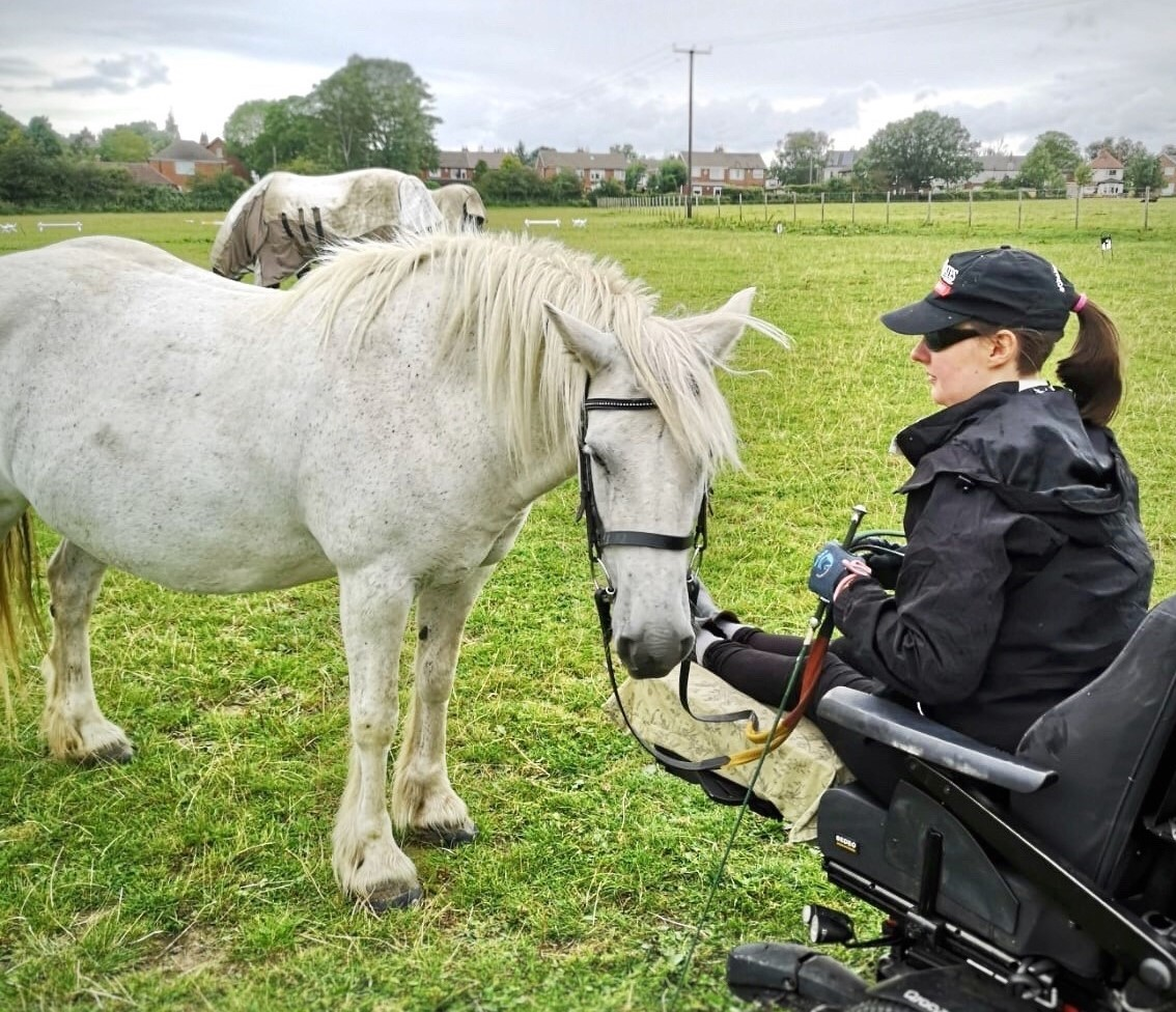 Groundwork. A girl sat in a Quickie Q700 Sedeo Pro wheelchair, holding the reins of a grey fell pony.