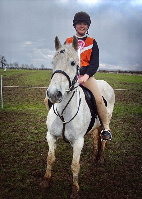 Mounted Games. A girl on a grey fell pony wearing an orange bib and a pink rosette, stood in a muddy field.