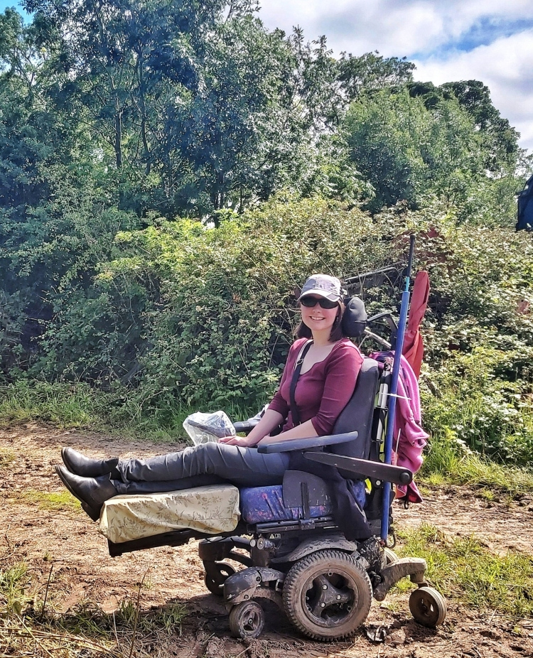 Holly, a white woman with shoulder length brown hair, sitting outside in front of hedges and trees in a Quickie Q700 Sedeo Pro Powered Wheelchair with the legs elevated. Wearing grey trousers, a plum coloured top, sunglasses and a grey baseball cap.