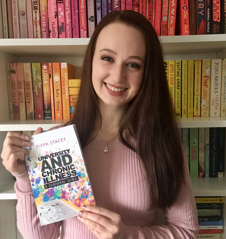 """Pippa, a white woman with long brown hair, smiling in front of a bookcase with a rainbow of books while holding the book """"University and chronic illness, a survival guide""""."""