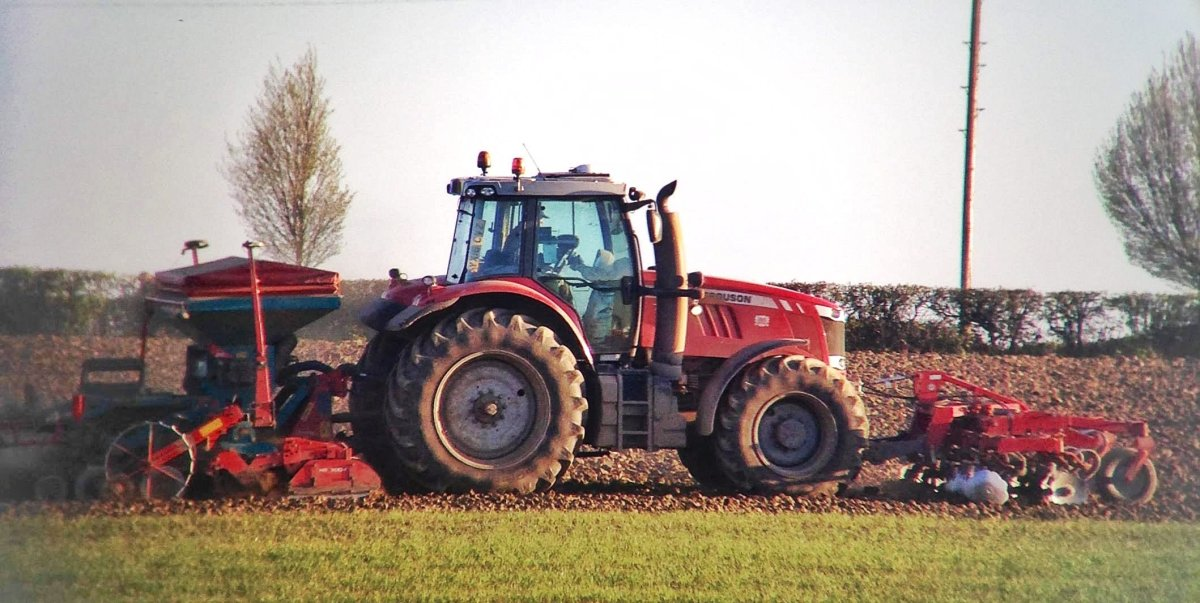 A red Massey Ferguson tractor driving across a field, with a set of discs on the front and a powerharrow and drill behind, drilling a crop.